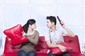 Couple fight on red sofa - indoor — Stock Photo