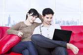 Couple looking at laptop in apartment on red sofa — Stockfoto