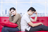 Couple stress sitting on red sofa — Stock Photo