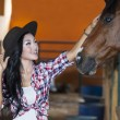 Asian woman touching horse — Stock Photo
