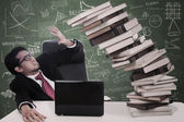 Stress businessman with falling books at class — Stock Photo