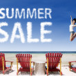 Advertising summer sale jump over beach chairs — Stock Photo #25327501