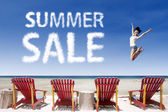 Advertising summer sale jump over beach chairs — Stock Photo