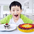 Boy laughing with desserts at home — Stok fotoğraf