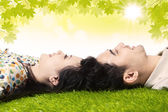Happy couple with heads together under leaves — Stock Photo