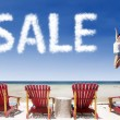 Advertising sale jump over beach chairs — Stock Photo #25654501