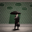 Businessman using umbrella to protect business loss — Stock Photo