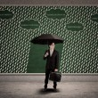 Stock Photo: Businessmusing umbrellto protect business loss