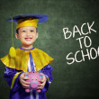 Foto Stock: Happy scholar dressed toddler with piggybank
