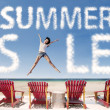 Summer sale cloud with girl jumping over beach chairs - Stock Photo