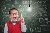 Asian boy has idea under lit bulb in classroom — Stock Photo