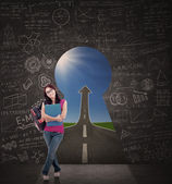 Beautiful female student standing in front of keyhole of success — Stock Photo
