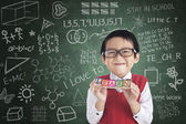 Cheerful boy student holding LEARN block — Stock Photo