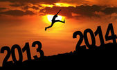 Amazing silhouette of man jumping at sunset toward 2014 — Stock Photo