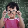 Cute girl holding glasses at class — Stock Photo #26338515