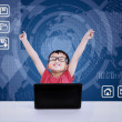 Asian boy winning using laptop on blue background — Stock Photo