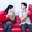 Angry couple on red sofa at apartment — Stock Photo