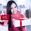Attractive female shopper show gift card and box — Stock Photo