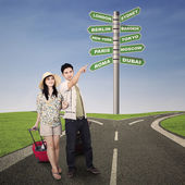 Asian couple travel with road signs outdoor — Stock Photo