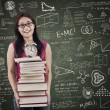 Asian female student bring stack of books in class - Stock Photo
