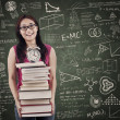 Asian female student bring stack of books in class — Stock Photo