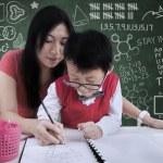 atraktivní učitel pomoci chlapce psát ve třídě — Stock fotografie #26616983