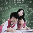Boy and his sister study in class with teacher — 图库照片