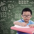 Boy writing on book in classroom — Stock Photo