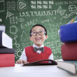 Asian boy laughing in class with stack of books — Stock Photo