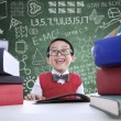 Asian boy laughing in class with stack of books — Stock Photo #26618221