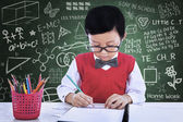 Asian boy drawing on paper in class — Stock Photo