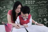 Çekici öğretmen sınıfta yazmak için bir çocuk yardım — Stok fotoğraf