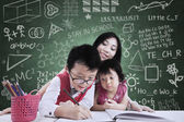 Boy and his sister study in class with teacher — Stock Photo