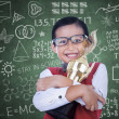 Stock Photo: Asian boy holding trophy in class
