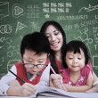 Beautiful teacher see children writing in class — Stockfoto