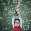 Happy boy raising trophy in class — Stock Photo