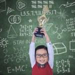 Happy boy raising trophy in class — Stock Photo