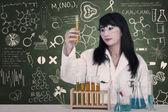Vackra läkare titta på flytande kolvar på laboratorium — Stockfoto