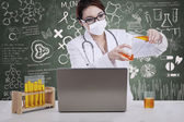 Beautiful female scientist pour liquid with written chalkboard — Stock Photo