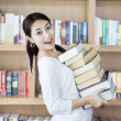 Attractive female bring stack of books in library — Stock Photo