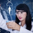 Attractive female scientist using pipette on blue background — Stock Photo #26847205