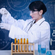 Beautiful doctor analysing liquid on blue — Stock Photo