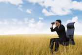 Businessman using binoculars on wheat field — Stock Photo