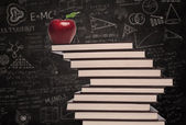 Apple education symbol and stack of books in class — Stock Photo