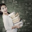 Attractive female bring pile of books in class — Stock Photo