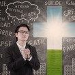 Businessman praying on chalkboard and cross background — ストック写真