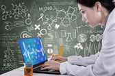 Beautiful scientist working with laptop at workplace — Stock Photo