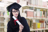 Beautiful woman in graduation gown pose at library — Stock Photo