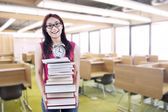Happy female student bring stack of books and clock — Stock Photo