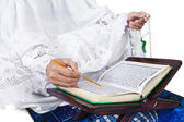 Close-up female muslim reading Quran on white — Stock Photo